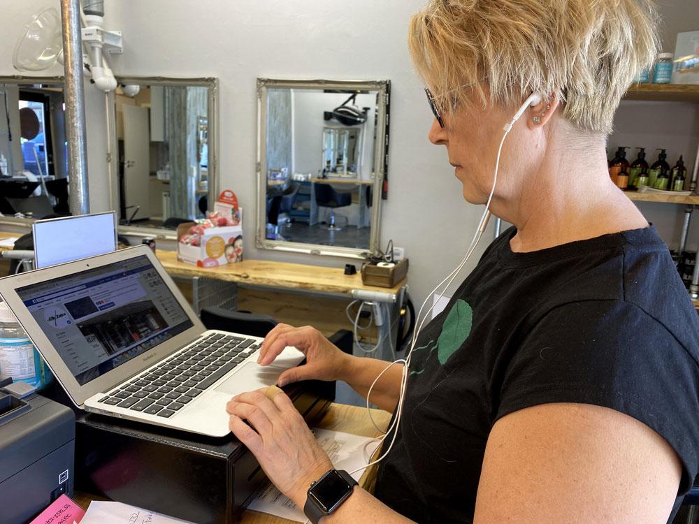 Jeanne sidder ved sin computer med høretelefoner på