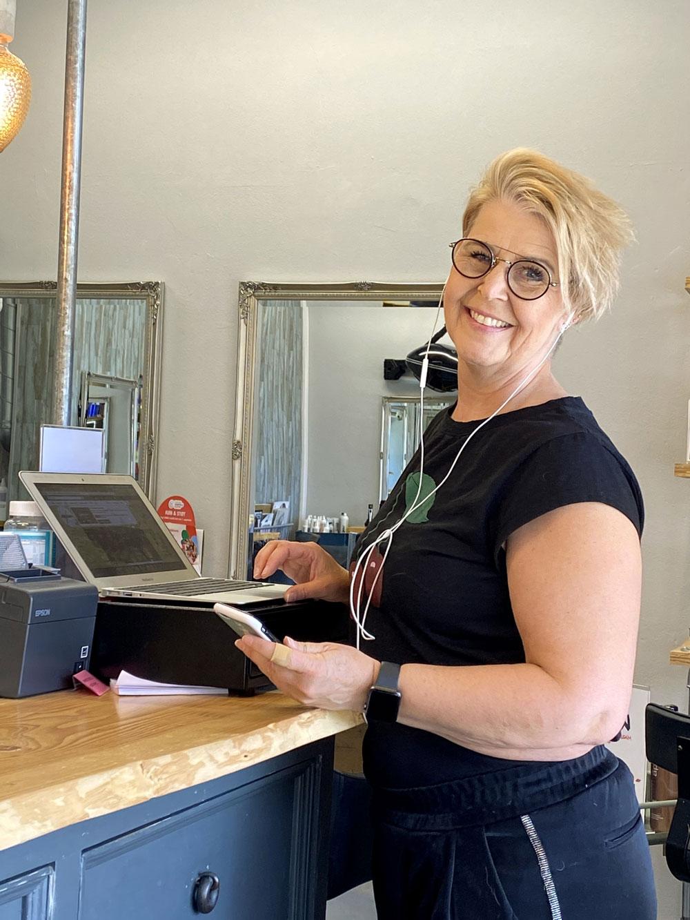 Jeanne står ved sin computer og smiler